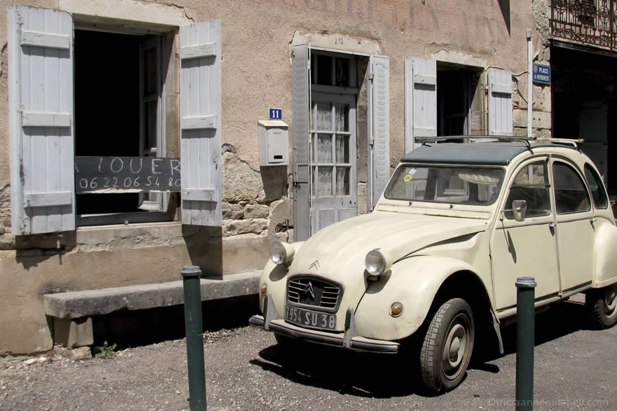 Citroën car parked in front of old French home.