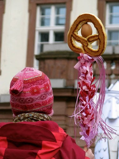 A child participating in Heidelberg's Sommertagszug festival, which celebrates spring's arrival, holds a pretzel and egg decoration on a stick.