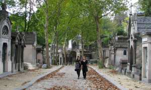 Two women stroll along a lane in Paris' Père Lachaise Cemetery. On either side of the lane there are grey mauseoleums. The street is partially covered with brown autumn leaves.