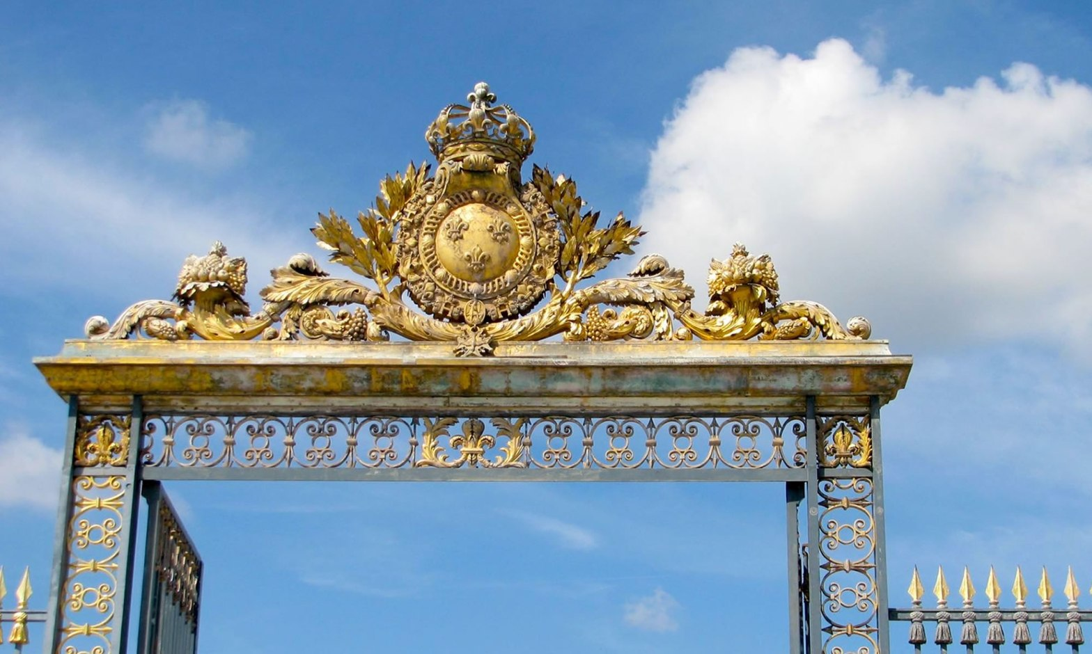The golden entryway to the Versailles Palace, on a blue sky day.