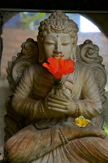 A statue seated in lotus position holds a red hibiscus flower.