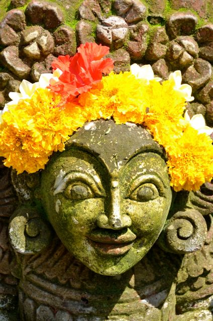 "A statue wearing a marigold ""crown"" in Bali."