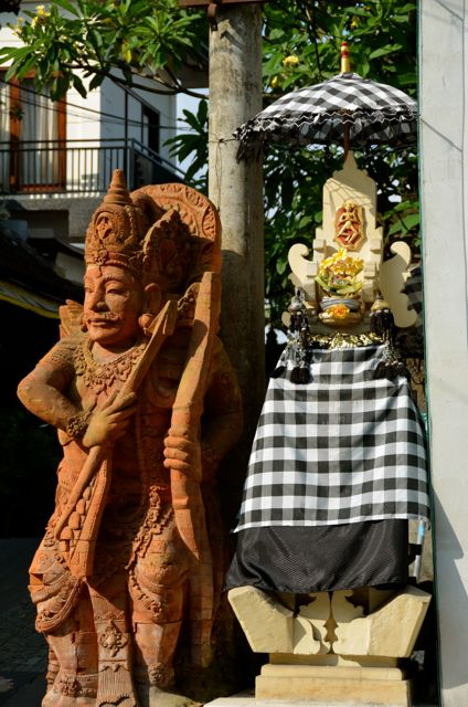An orangish-brown Balinese statue stands beside a shrine.
