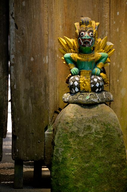 A green and gold Balinese statue stands in front a wooden building.
