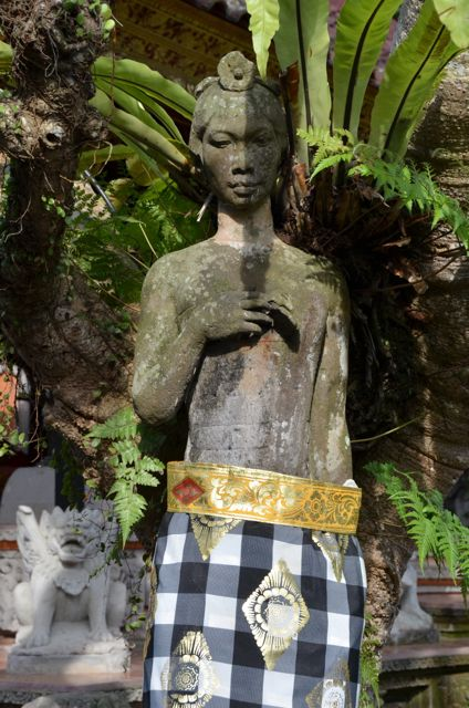 Black and white fabric is draped around the waist of a Balinese statue.
