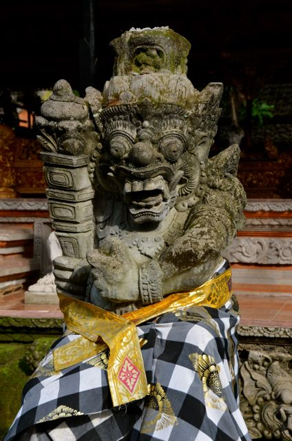 A Balinese statue draped with black and white fabric.