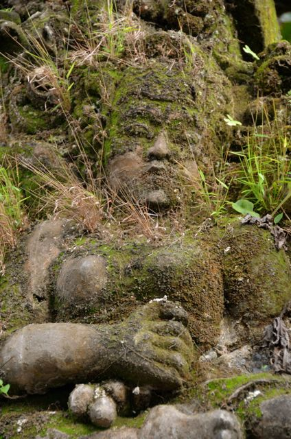 A statue in Bali overgrown with grass and moss.