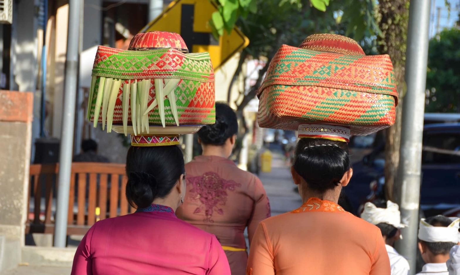 Women balance spiritual offering baskets on their heads in Ubud, Bali.