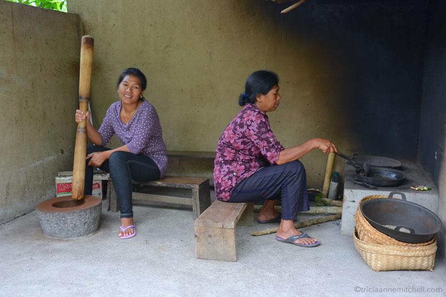 Two women roast 'weasel coffee' beans at the Wedang Sari coffee plantation in Bali.