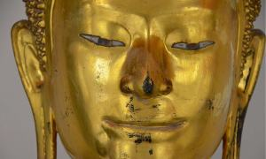 Close up of a golden Buddha statue's eyes, ears, nose and mouth.