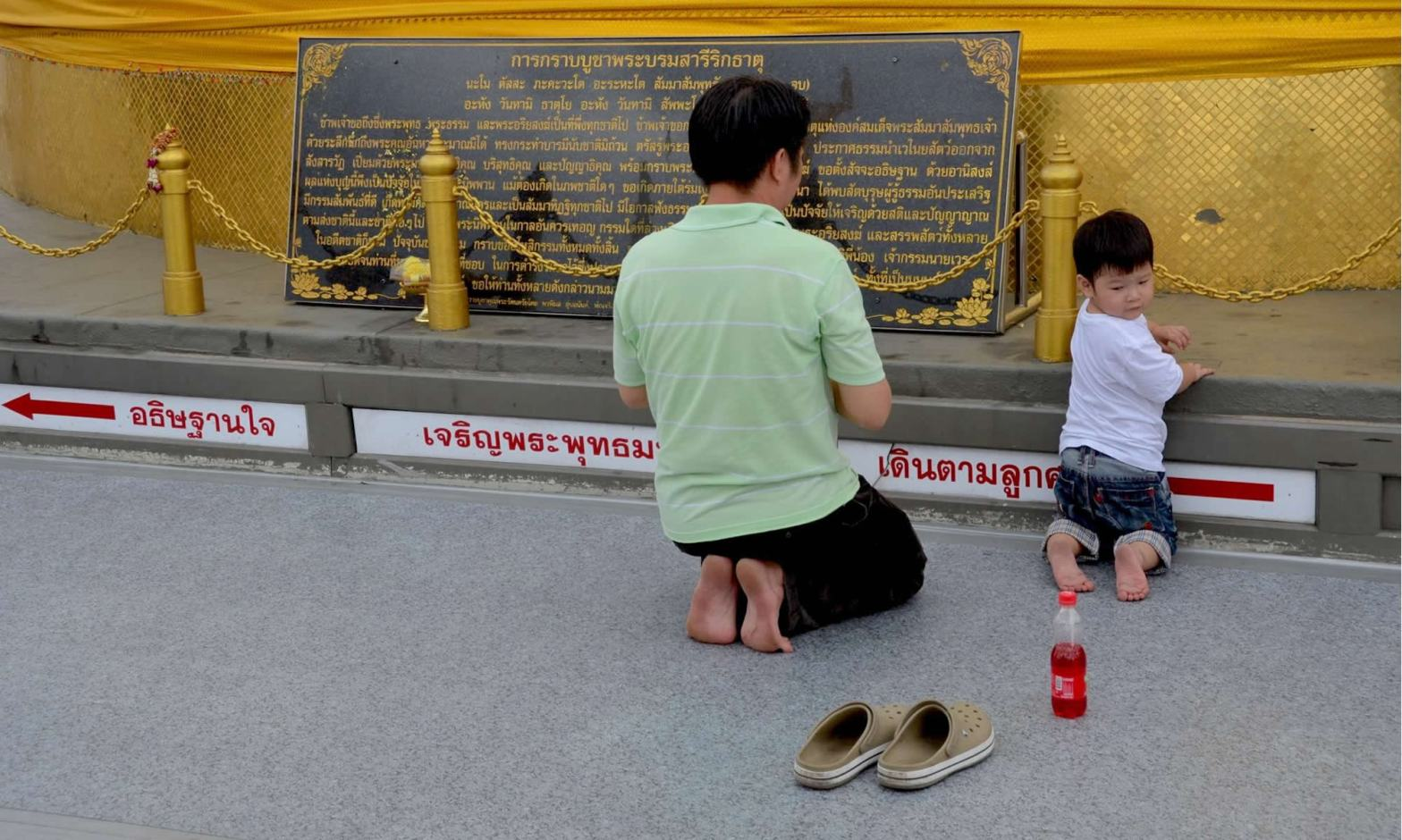 As the adult next to him prays at Bangkok's Golden Mount, a young boy is distracted by a bottle of soda.