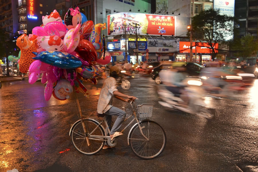 A young made riding a bike - decked out in helium balloons - tries to cut through night-time traffic in Ho Chi Minh City.