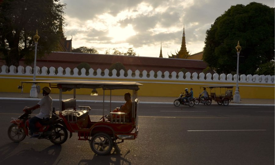 Tuktuks pass by the exterior of Phnom Penh's Royal Palace, just before sunset.
