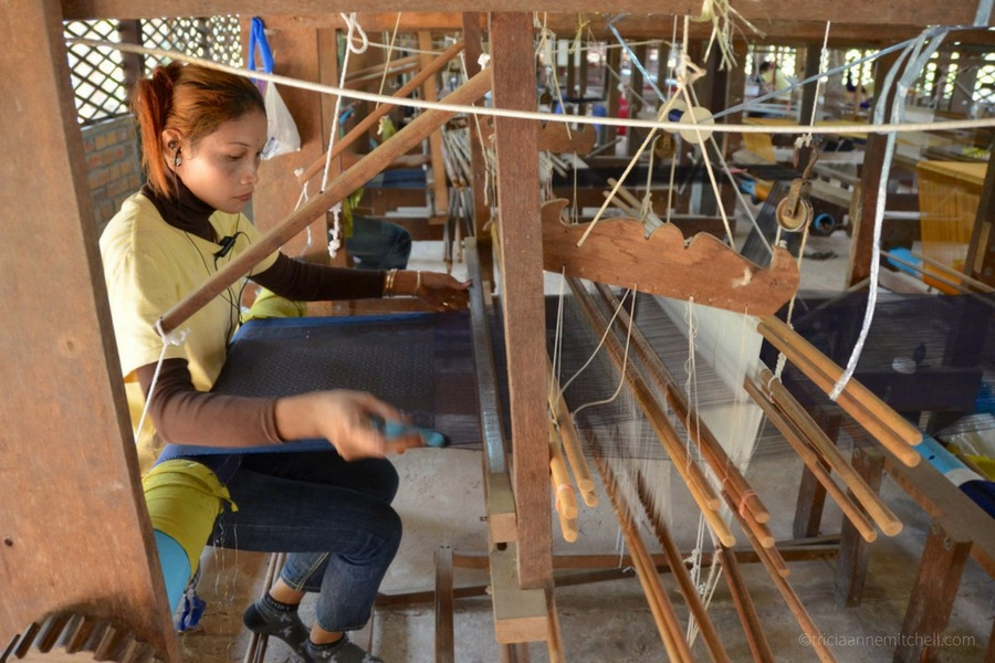 A woman operates a floor loom weaving silk for a traditional Cambodian Ikat.