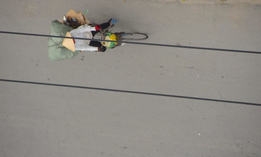 A woman bikes along a street in Nha Trang, Vietnam.