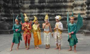 Six adults, dressed in traditional Cambodian costumes, stand near Angkor Wat.