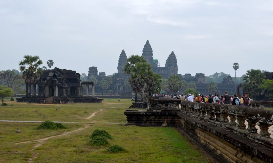Tourists walk toward Angkor Wat in Cambodia.