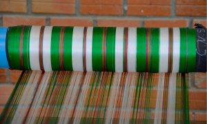 Green and white silk thread is guided onto a roll on a silk farm near Siem Reap, Cambodia.