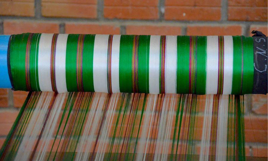 Green and white silk thread is guided onto a roll on a silk farm near Siem Reap, Cambodia.