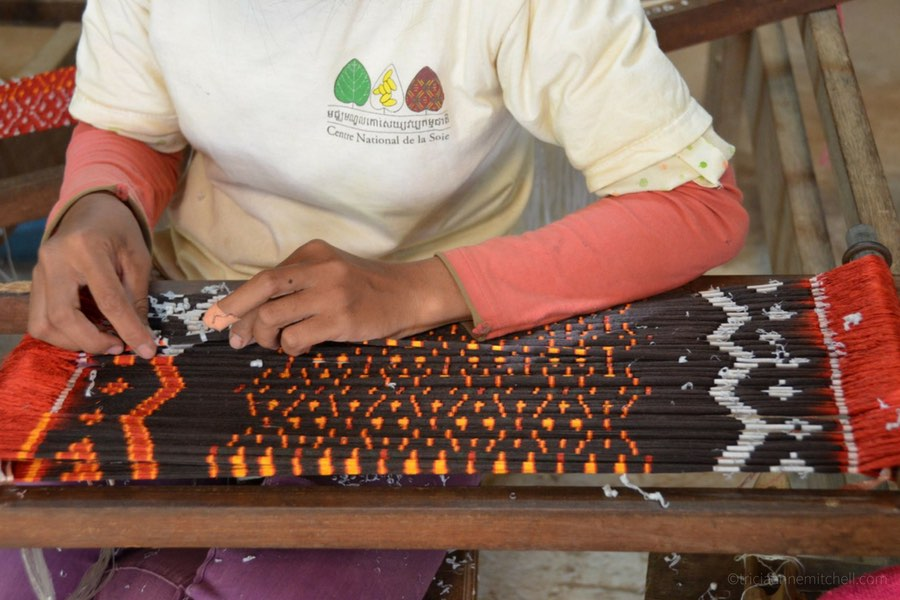 A woman at a Siem Reap, Cambodia silk farm performs the meticulous task of coloring silk thread for Ikat fabric.