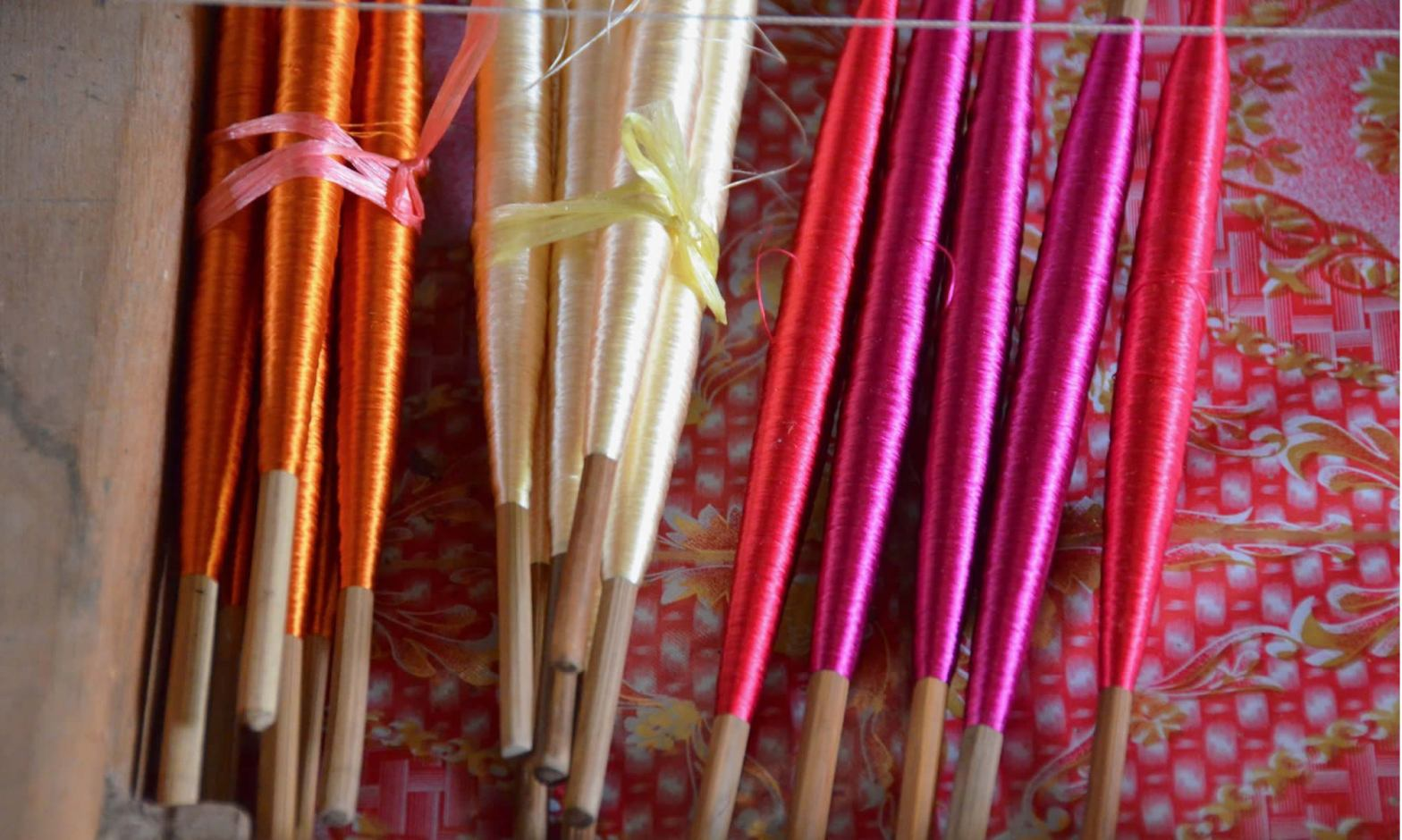 Bobbins of orange, cream, and fuchsia silk inside a drawer at a silk farm near Siem Reap, Cambodia