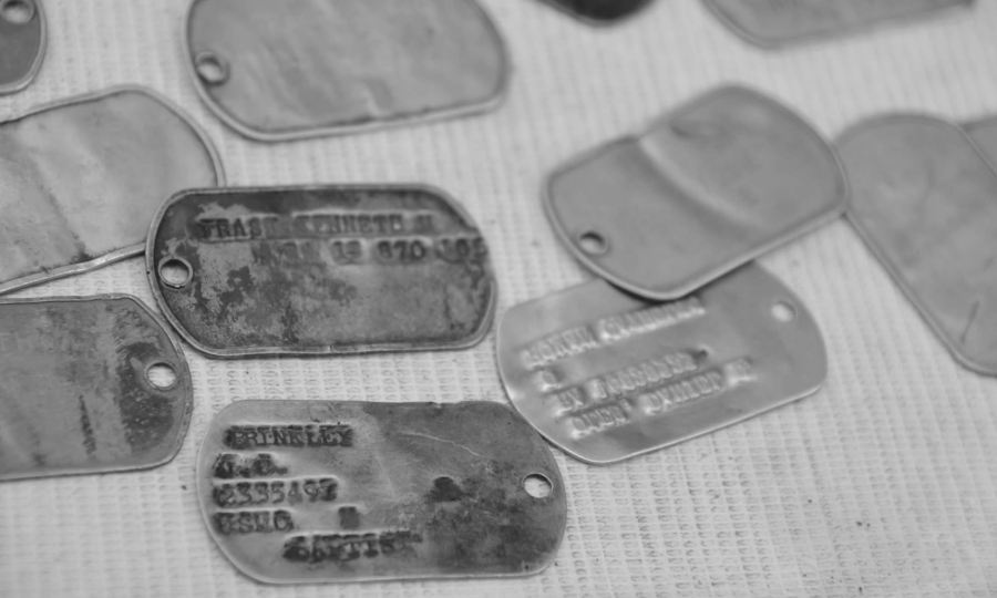 A black and white image of dog tags for sale at an outdoor market in Hue, Vietnam. They supposedly date to the Vietnam War.