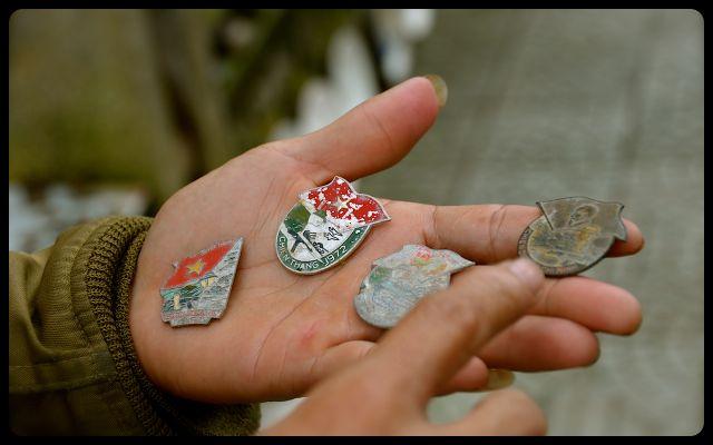 man holds war medals in hand, in Hue, Vietnam
