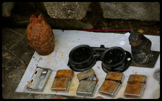 rusty grenade and cigarette lighters for sale on Vietnamese sidewalk