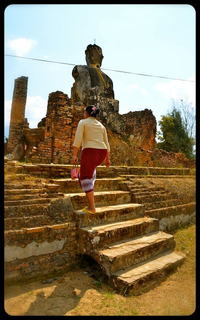 A woman climbs the steps at the ruined Wat Piha Wat Temple in Laos.