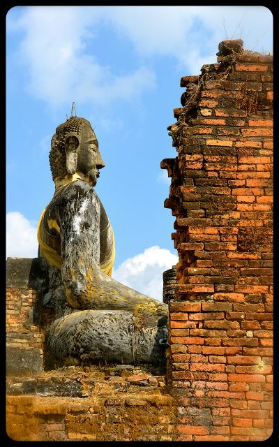 A damaged wall and Buddha statue at Laos' Wat Phia Wat Temple.