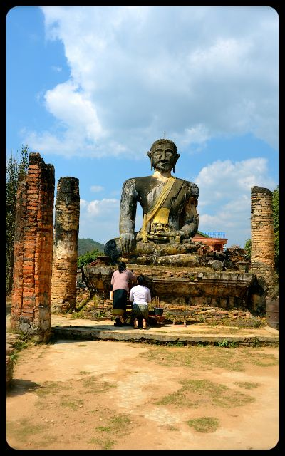 Two women pray at the foot of a damaged Buddha at Wat Phia Wat in Laos.