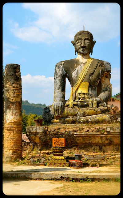 A damaged Buddha rises from the ruins of Wat Phia Wat in Laos.