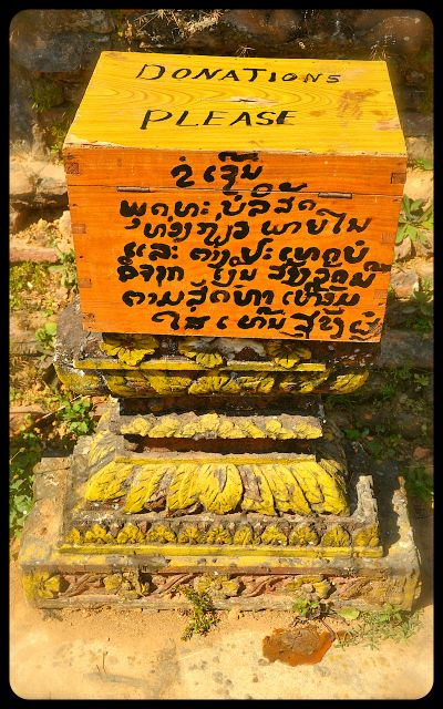 "A donation box at the damaged Wat Phia Wat Temple in Laos. The writing on the box is English and Laotian. The English says, ""Donations Please."""