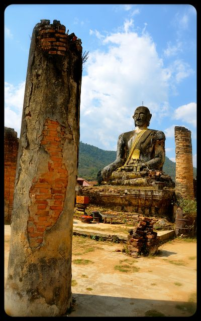 A ruined column and the damaged Buddha statue at Wat Phia Wat in Laos.