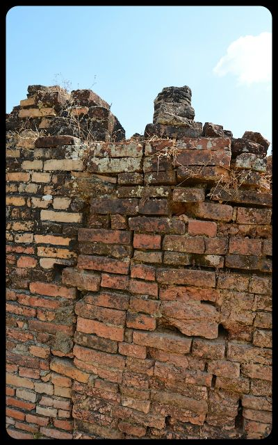 The remains of a reddish-orange brick wall at the Wat Phia Wat Temple in Laos.
