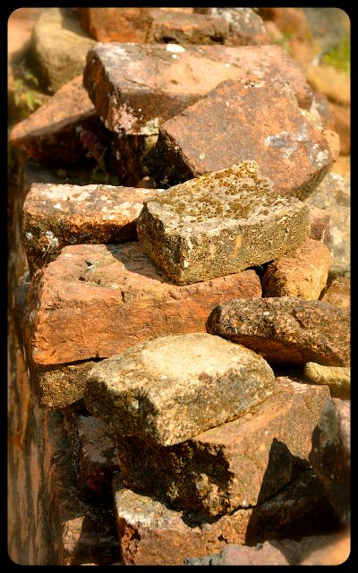 A pile of orange-red bricks at the Wat Phia Wat Ruins in Laos.