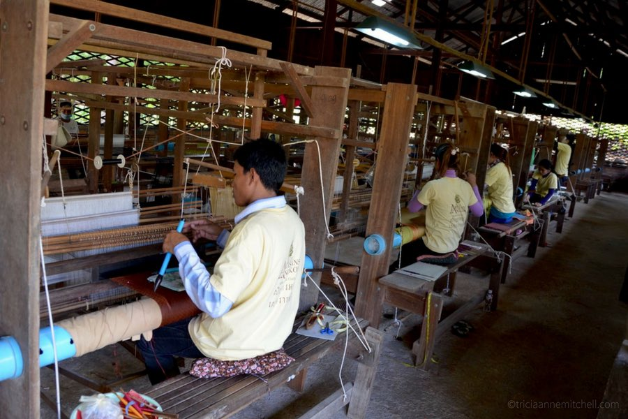Cambodian male and female employees weave silk fabric