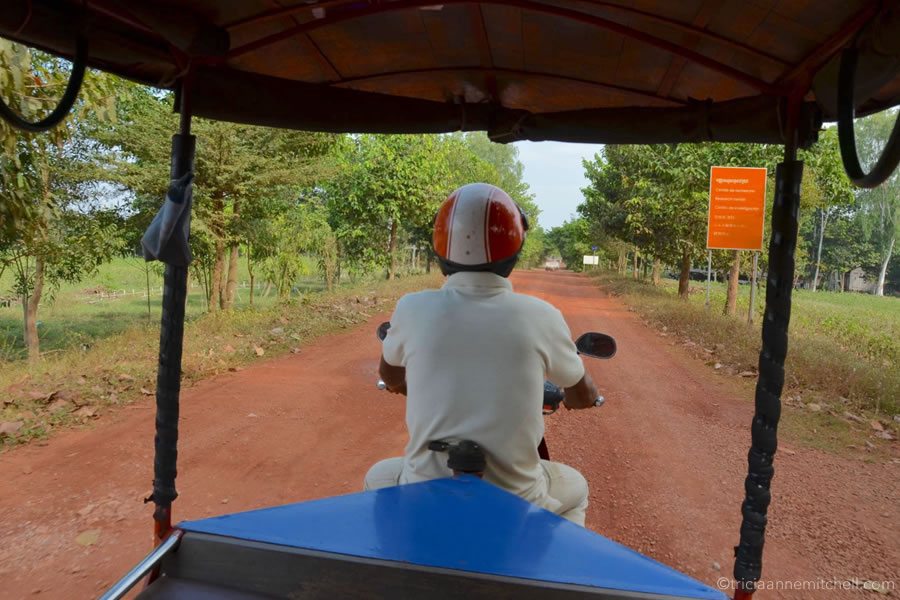View from the back of a Cambodian tuktuk, driving on a red dirt road.