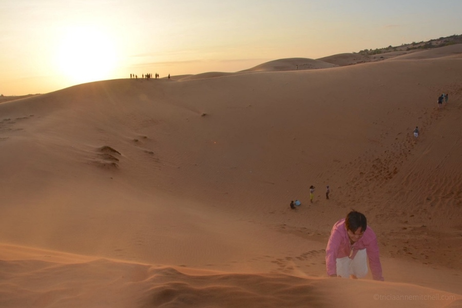 A man climbs Mui Ne's sand dunes on his hands and knees.