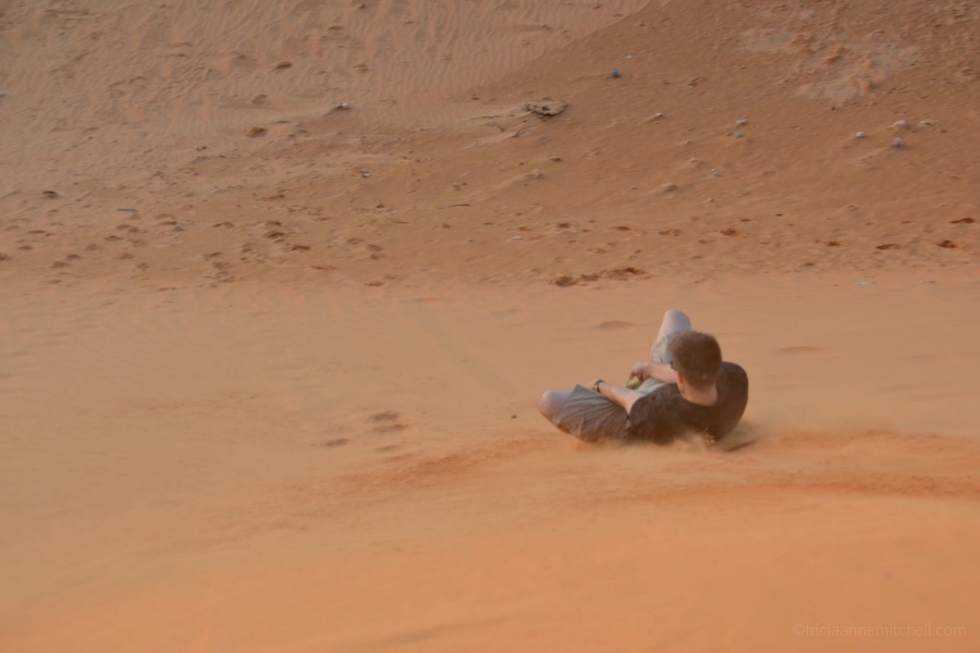 man sandboarding Mui Ne Sand Dunes Vietnam