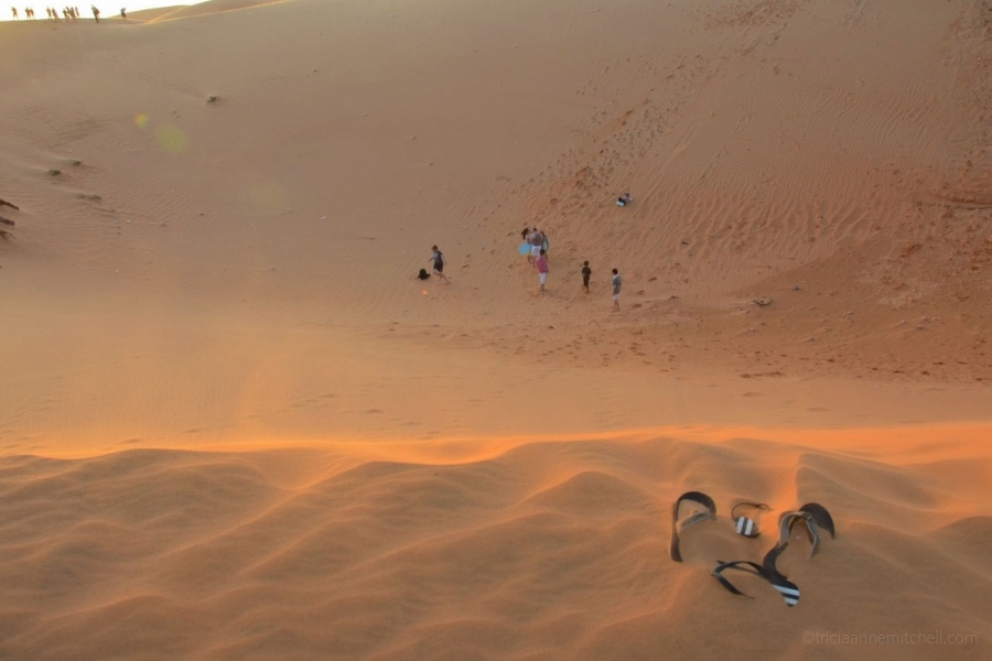 Flip flops, submerged in sand, sit on Mui Ne's Red Sand Dunes.