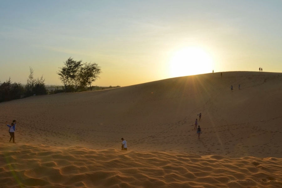 People walk across Mui Ne's sand dunes at sunset.