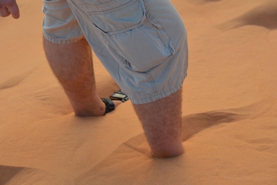 A man's legs are submerged in sand at the Mui Ne Red Sand Dunes in Vietnam.