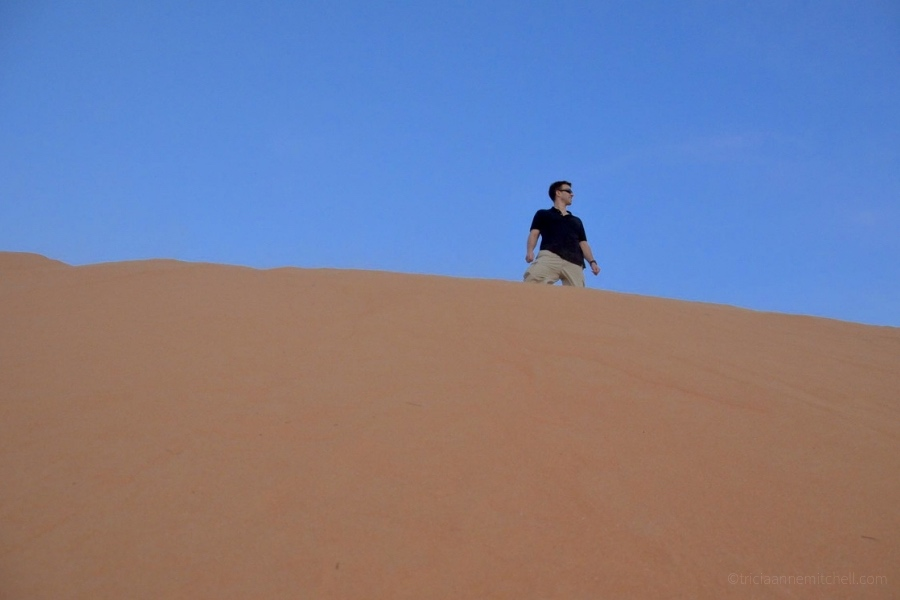 A man stands atop the Mui Ne Sand Dune in Vietnam with a blue sky overhead.