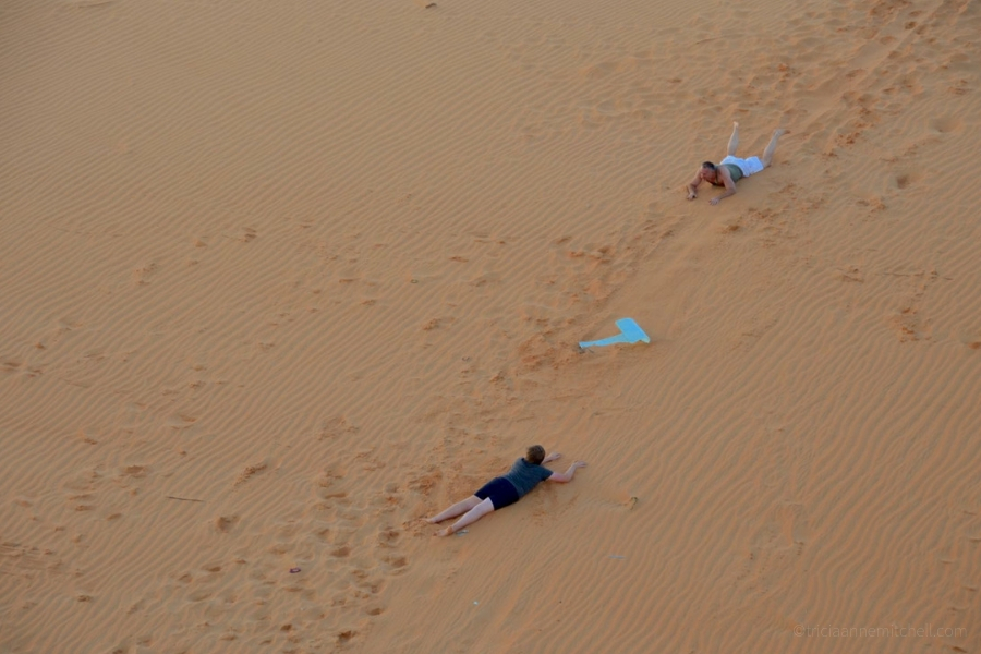 People sled on the Mui Ne sand dunes at sunset.