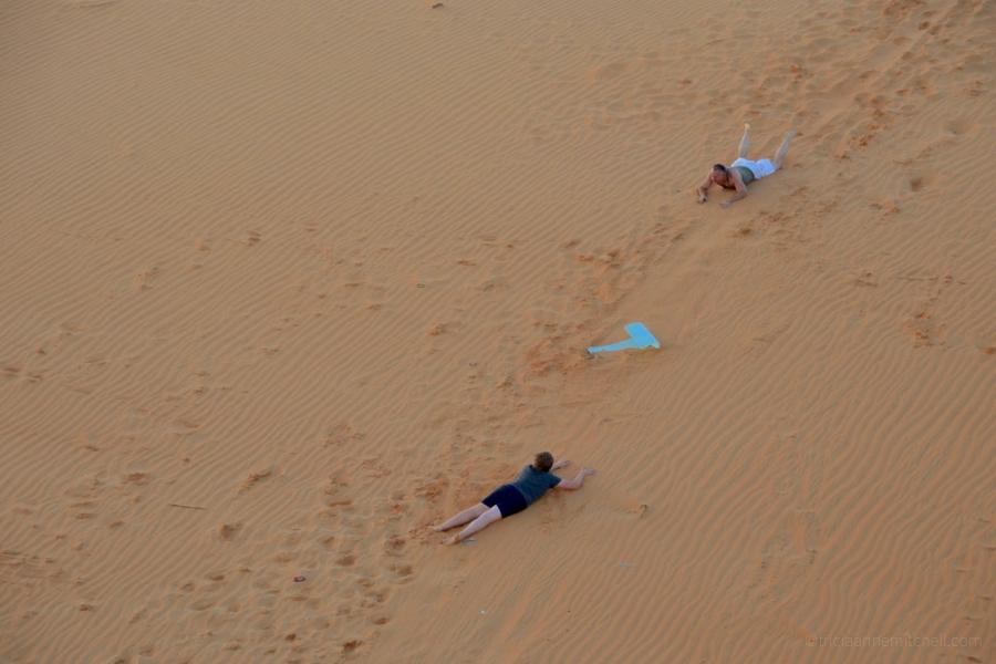 People sled on the Mui Ne sand dunes at sunset.