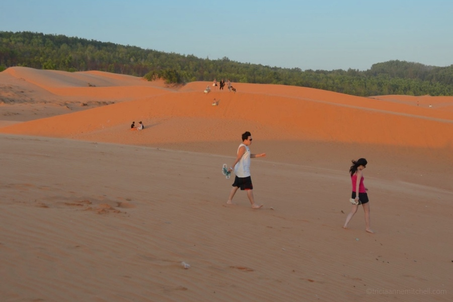 A couple walks across the Mui Ne Sand Dunes at sunset.