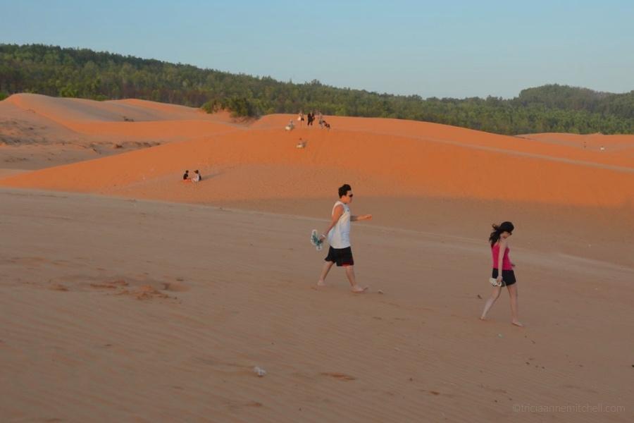 A couple walks across the Mui Ne Sand Dunes at sunset.