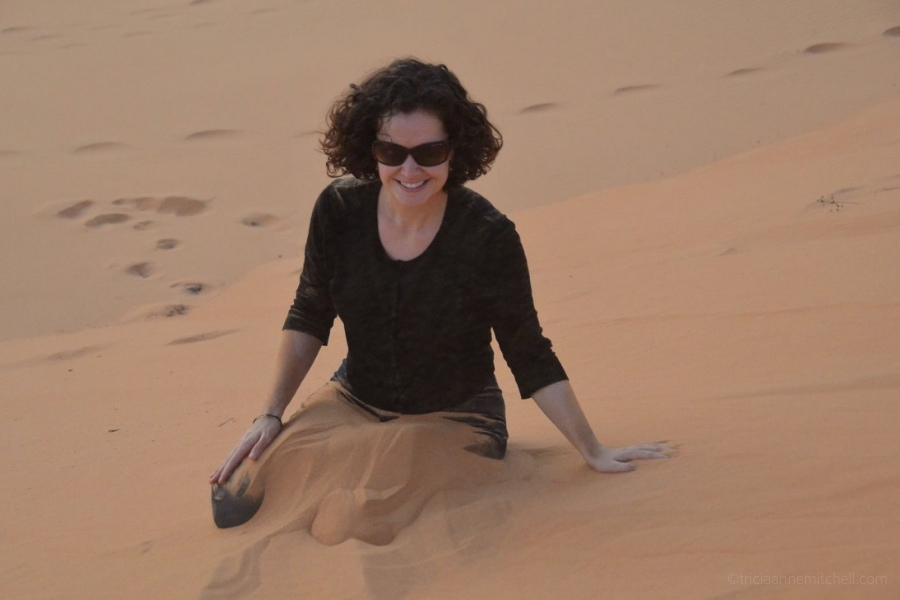 A woman sits on the Mui Ne Sand Dunes. Her legs are submerged in sand.