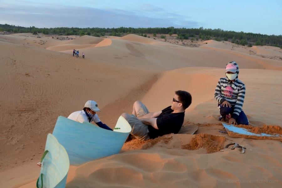 A man sandboards on Mui Ne's Red Dunes.